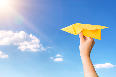 paper travel sky plane child flying yellow fun human leisure kid throw view throwing handmade freedom object up air airline joy concept - stock image Stock Photo