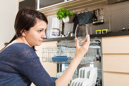 domestic kitchen: Woman using a dishwasher in a modern kitchen. Domestic appliance.