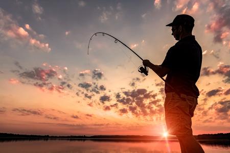 river: fishing rod lake fisherman men sport summer lure sunset water outdoor sunrise fish - stock image  Stock Photo