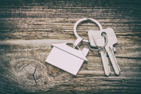 secure: House key on a house shaped keychain on wooden table. Concept for real estate or renting home.