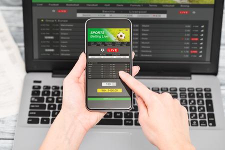 Apuestas deportivas apuesta apuesta de teléfono portátil sobre el hombro de fútbol en directo concepto de inicio del sitio web - Imagen Foto de archivo