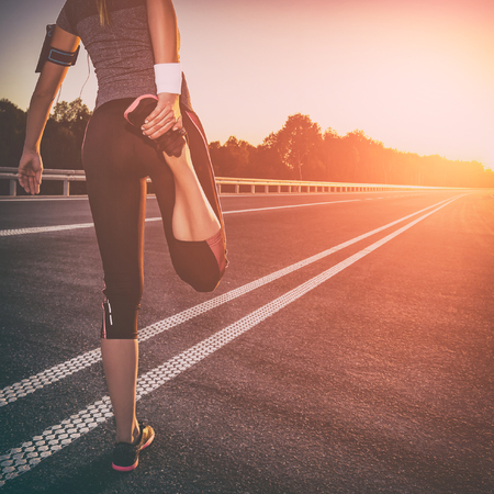 stretching run runner exercise road jogging flare sunset fitness cross sunbeam success running sportswear - stock image Stock Photo