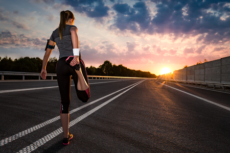 stretching run runner road jogging clothes flare sunset street fitness cross sunbeam success running sportswear - stock image Stock Photo