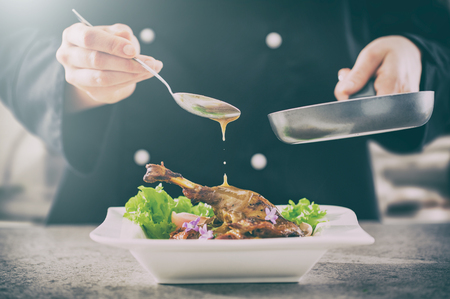 chef cooking restaurant food salad sauce gourmet molecular decorating kitchen dish garnish plate serving lunch top dinner concept - stock image