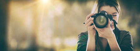 female photographer: Portrait of a photographer covering her face with the camera.