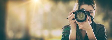 Portret fotografa obejmujące jej twarz z aparatem. Zdjęcie Seryjne
