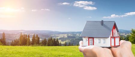Logement maison main main réelle tenant herbe verte ciel bleu image stock Banque d'images