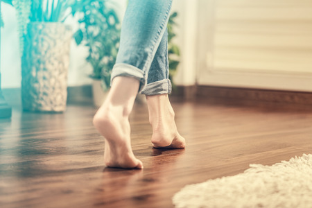Floor heating. Young woman walking in the house on the warm floor. Gently walked the wooden panels. Stock fotó - 73650982