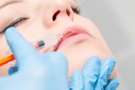 woman fillers spa facial young treatment syringe injecting injection skin lips concept - stock image