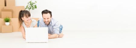Een jonge kinderen zitten in een nieuw appartement en maakt gebruik van een laptop. Bespreek huis reparatie projecten tijdens het verplaatsen. Stockfoto