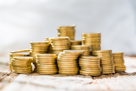 capital gains: golden coin money stack save savings profit wooden table - stock image