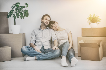 furnish: A young couple sitting on the floor and looking up. Dream and enjoy your new home.