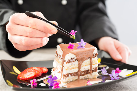 adding: chef chocolate pastry dessert flower plate fine garnish icing making cake cooking food perfect dining adding building concept - stock image