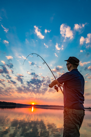 summer sport: fishing rod lake fisherman men sport summer lure sunset water outdoor sunrise fish - stock image