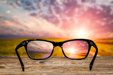 farsighted: glasses focus background wooden eye vision lens eyeglasses nature reflection look looking through see clear sight concept transparent sunrise prescription sunset vintage sunny sun retro - stock image