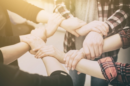 trust people: A group of young people hold strong hands. Sign of trust and teamwork.