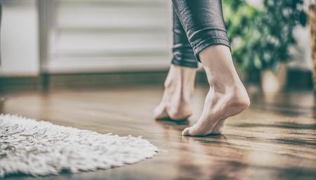 Calefacción por suelo. Joven mujer caminando en la casa en el piso caliente. Caminamos con delicadeza por los paneles de madera. Foto de archivo