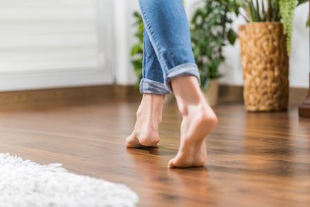 Podlahové topení. Mladá žena chodí v domě na teplé podlaze. Mírně prošel dřevěnými panely. Reklamní fotografie