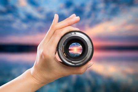 사진보기 렌즈 사진을 통해 렌즈 렌즈 손을 통해 디지털 손 유리 흐리게 초점 일출 일몰 일출 클라우드 하늘 물 호수 개념 - 재고 이미지 스톡 콘텐츠