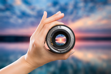 photography view camera photographer lens lense through video photo digital glass hand blurred focus people sun sunset sunrise cloud sky water lake concept - stock image