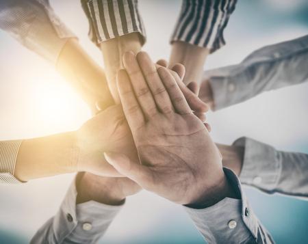 즐기고 팀 작업의 성공을 축하하는 사업 사람들의 그룹. 그들은 승리의 몸짓으로 손을 위로 향하게합니다.