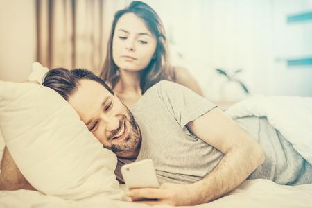 Ein junges Paar im Bett liegen. Einer von ihnen das Telefon und flirtend verwenden. Die andere Person ist eifersüchtig und Spione des Armes. Das Konzept der Eifersucht und Misstrauen. Standard-Bild - 75086142