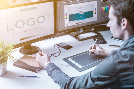 Computer graphic designer designs logos and advertising graphics. Draws a logo on the graphics tablet. Banque d'images