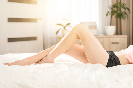 Portrait of a woman lying on a bed. Beautiful legs in the main set. Banque d'images