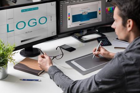 Computer grafisch ontwerper ontwerpt logo's en reclame graphics. Tekent een logo op de grafische tablet. Stockfoto