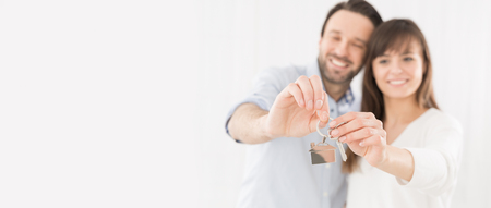 手の家の鍵を保持している若いカップル。新しいアパートの喜び。 写真素材 - 77234974