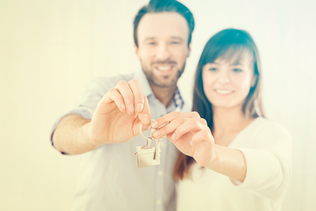 A young couple holding hands house key. The joy of a new apartment. Banque d'images
