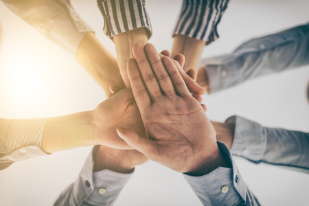 trust people: Business people hands stacked in a pile. A symbol of teamwork and trust.