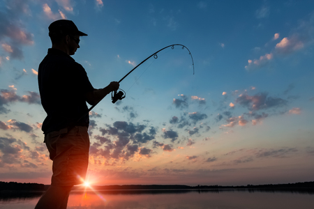 fishing rod lake fisherman men sport summer lure sunset water outdoor sunrise fish - stock image