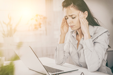 Young woman is tired and feels stressed out. Frustrated, she closed eyes and massage temples head.