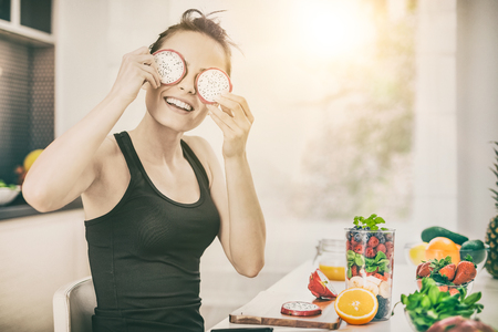 Happy young woman puts slices of dragon fruit as glasses. Healthy Eating - concept.