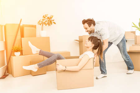 Young couple people have fun while moving to a new apartment. Boy pushes box with the girl. Happy people in the new house. Banque d'images