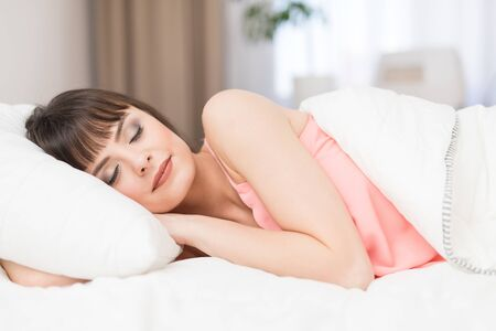 nightwear: Beautiful young woman sleeping on a bed in the bedroom. A peaceful sleep makes you happy.