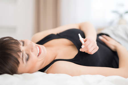 bedroom: Young beautiful woman holding a pregnancy test. Enjoys a positive result. He is happy because he will be a mom.