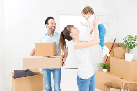 box: Young family with a child moves to a new apartment. Parents and daughter are happy. The girl pushes box. The concept of a new home.