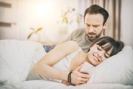 desconfianza: Una pareja joven tumbado en la cama. Uno de ellos utilizan el teléfono y flirteo. La otra persona es celosa y espías del brazo. El concepto de los celos y la desconfianza. Foto de archivo