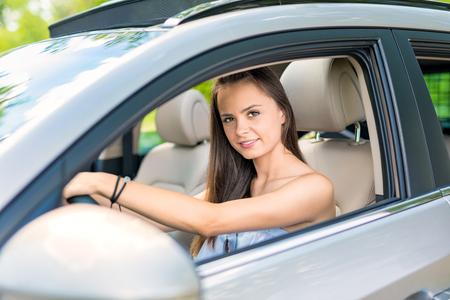 Belle jeune femme assise à l'intérieur d'une nouvelle voiture avec un sourire. Il est heureux qu'il soit un conducteur.