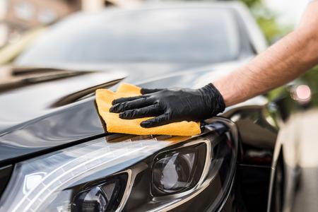 詳しく述べる車 - 男、マイクロファイバーを手で保持しているし、車を磨きます。選択と集中。
