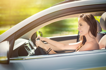 Beautiful young woman sitting in the interior of a new car with a smile. He is glad he is a driver. Banque d'images