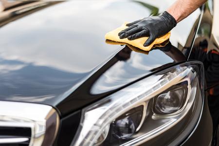 Car dettaglio - l'uomo tiene il microfibra in mano e lucida l'auto. Messa a fuoco selettiva. Archivio Fotografico - 82172123