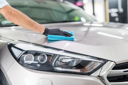 Car dettaglio - l'uomo tiene il microfibra in mano e lucida l'auto. Messa a fuoco selettiva. Archivio Fotografico - 82172126