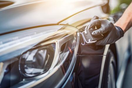Detalles del automóvil: el hombre aplica una capa protectora nano al automóvil. Enfoque selectivo. Foto de archivo - 82172131