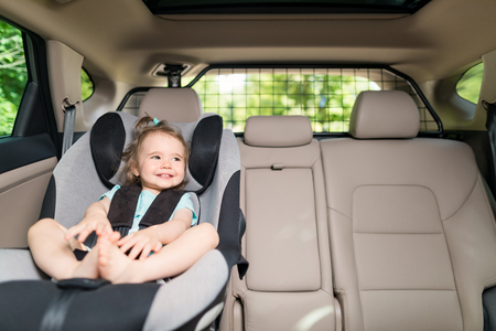 Beautyful smiling baby girl fastened with security belt in safety car seat Reklamní fotografie - 82172132