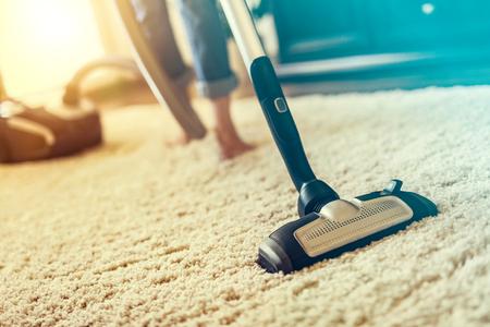 Jovem mulher que usa um aspirador de p30 ao limpar o tapete na casa. Foto de archivo
