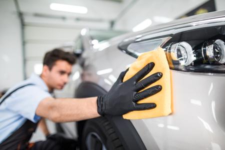 자동차 디테일 - 남자는 마이크로 화이버를 손에 들고 차를 닦는다. 선택적 포커스입니다. 스톡 콘텐츠