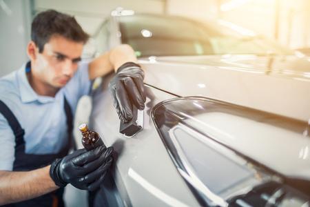 詳しく述べる車 - 男が車にナノの保護コーティングを適用。選択と集中。 写真素材